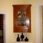 Hanging curly maple corner cabinet with glass door